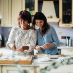A mother and daughter prepare healthy food in their kitchen.
